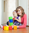 mother and baby girl plays with blocks in home
