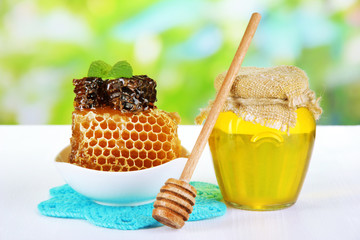 Sweet honeycombs in bowl and bank with honey