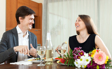 Young man and smiling woman having romantic dinner in home