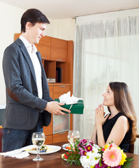 Guy giving a gift to a girl for a romantic dinner