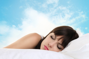 head girl sleeping on pillow with blue sky in background