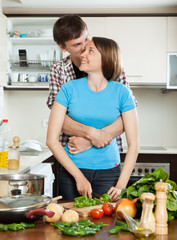 Young couple hugging in kitchen