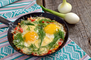 Fried eggs with greens, vegetables and cheese on a frying pan.