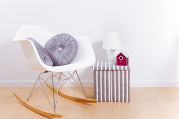 Modern white rocking chair and wall