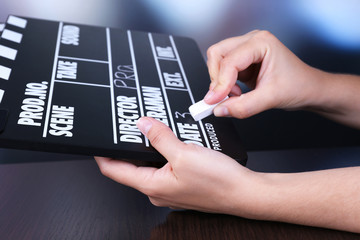 Black cinema clapper board in hands, close up
