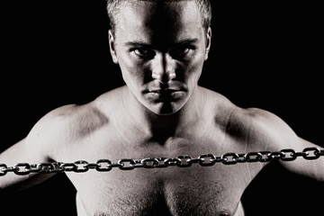 Close-up portrait of a young muscular guy with a metal chain.