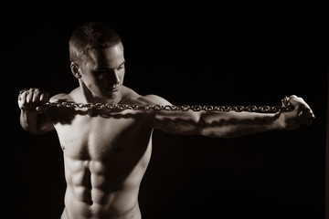 Portrait of a young muscular guy with a tight metal chain