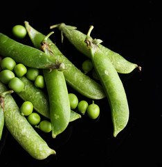 Fresh green peas isolated on black background