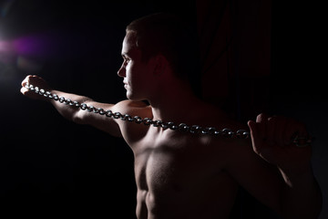 Portrait of a young muscular guy with a tight metal chain.