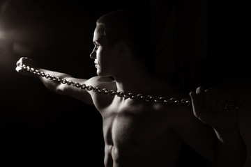Portrait of a young muscular guy with a tight chain