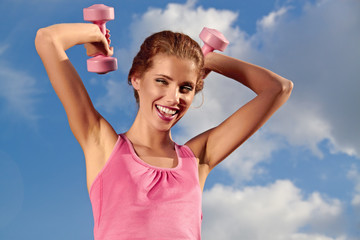 Pretty young woman exercising with small weights