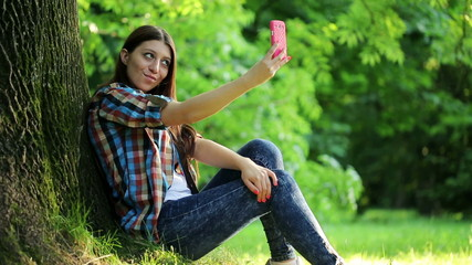 Teenager taking selfie photo in park with smartphone