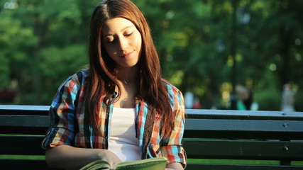Young female student reading book in the park