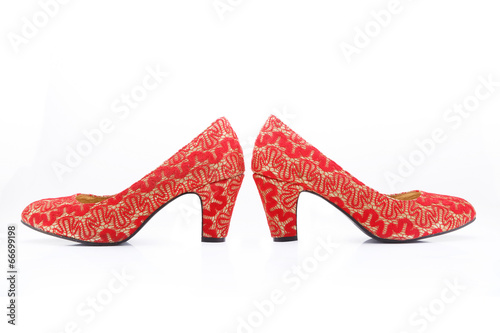 Beautiful chinese embroidered wedding shoes isolated on white © GUAN JIANGCHI