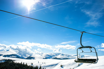 Mountain slopes with chairlift on a winter sunny day