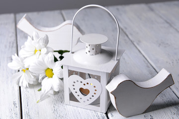 White lantern with flowers on wooden table, close-up