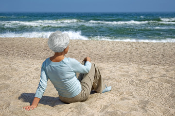 elderly woman sitting in the sand on the beach