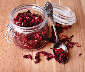 Dried hibiscus tea in glass jar on wooden background