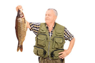 Proud mature fisherman holding a big fish