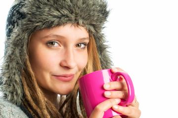 Frau mit Fellmütze hält Kaffeebecher