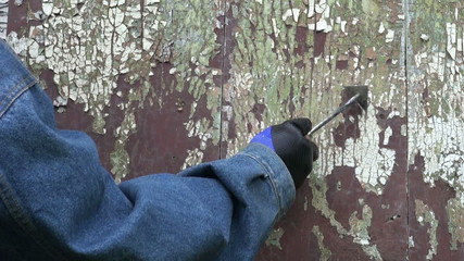 worker hand scrapping old cracked paint from wooden door