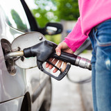 Lady pumping gasoline fuel in car at gas station. poster