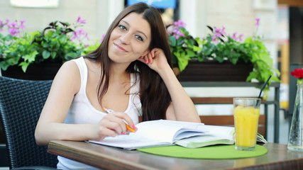 Portrait of young happy female student in cafe