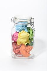 Hojas de papel de colores arrugadas en un bote cerrado