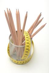 Bote con lapiceros y cinta de medir