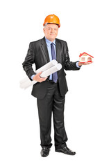 Mature architect holding plans and a small model house
