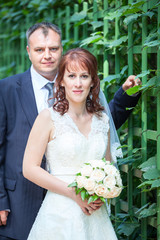 Wedding couple portrait with green fence