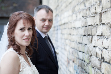 Faces of bride and groom against brick wall
