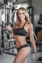 Blonde sexy bodybuilder workout with dumbbells