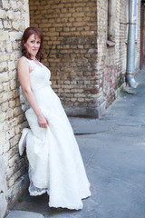 Bride leaning to brick wall