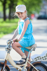 Side view of pretty girl riding on bicycle