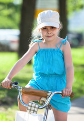 Small pretty girl riding bicycle
