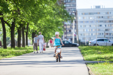 Girl riding bicycle in park at summer day