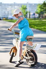 Girl on bike, turning back, looking at camera