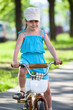 Beautiful girl in blue dress riding bicycle