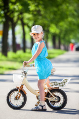 Girl riding on small two-wheeled bicycle