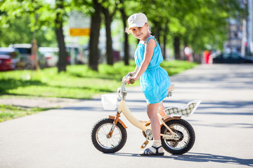 Pretty girl riding on small two-wheeled bicycle