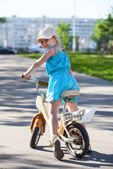 Little girl looking back over her shoulder, sitting on bicycle