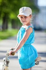 Girl in blue dress and white cap on bicycle