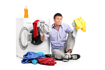 Confused young man doing laundry
