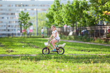 Child riding bike in summer day