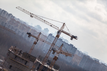Construction cranes over buildings