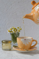 Pouring Chamomile Tea in an Orange Cup
