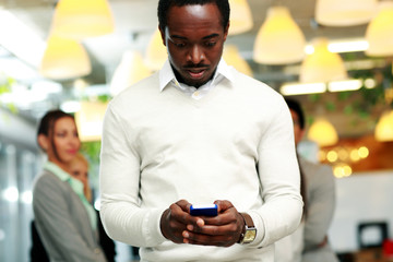 Surprised businessman using smartphone in front of colleagues