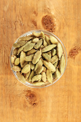 green cardamom in glass bowl on wooden background close-up