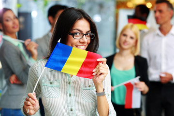 Happy businesswoman holding flag of Romania